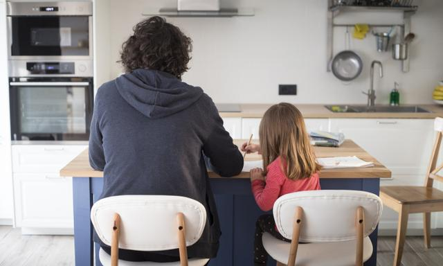 Young father working from home with little daughter during covid-19 lockdown. Child with dad smartworking in kitchen for social isolation.