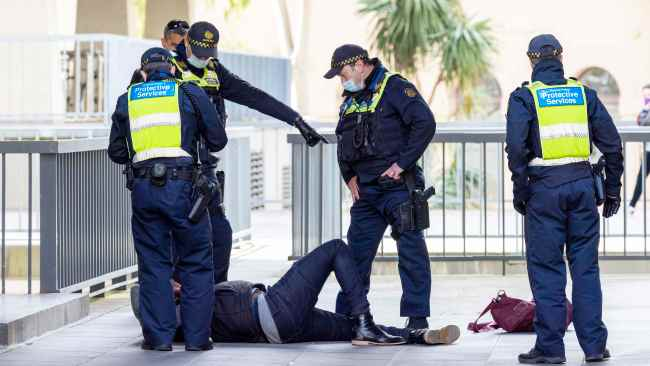 The protester claimed his leg had been broken when police tackled him and was later stretchered off the scene by paramedics. Picture: NCA.