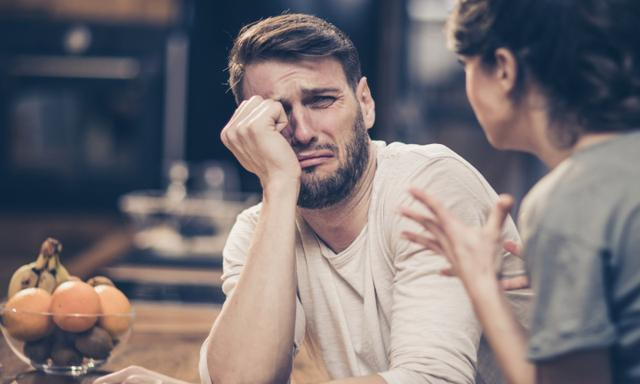 Depressed man feeling fear while his wife is angry at him.
