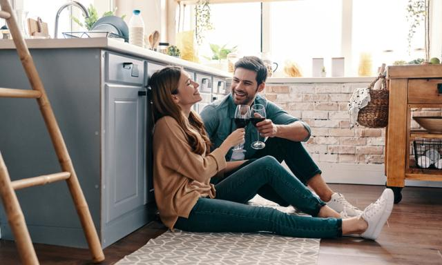 Beautiful young couple drinking wine while sitting on the kitchen floor at home