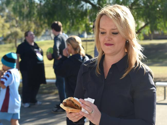 The taste of defeat? Fiona Scott assesses a sausage sandwich after casting her vote. Picture: AAP Image/Paul Miller