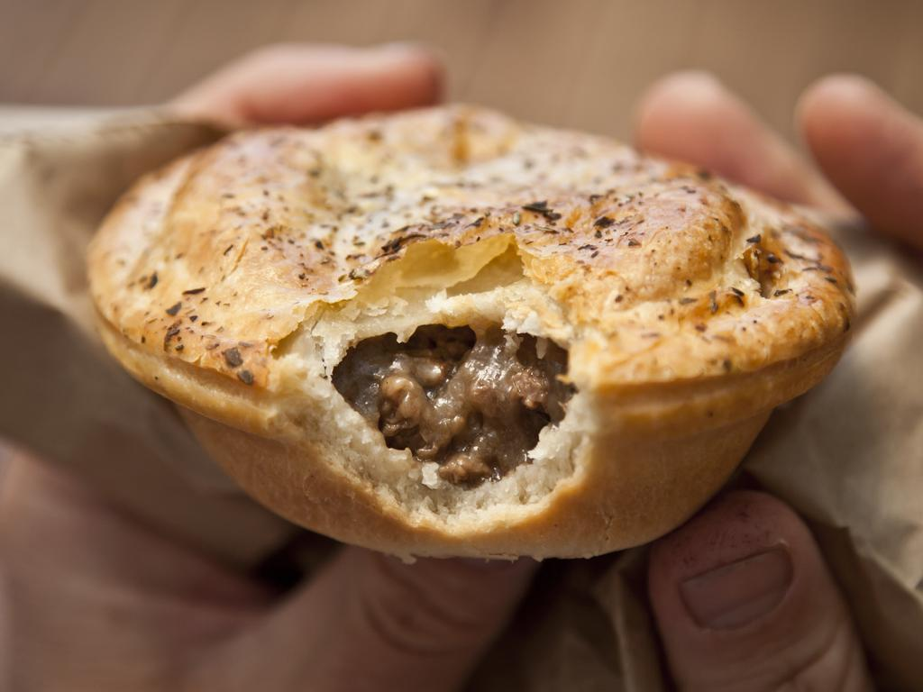 Close-up of a man's hands holding an Australian meat pie with a bite taken out of it.