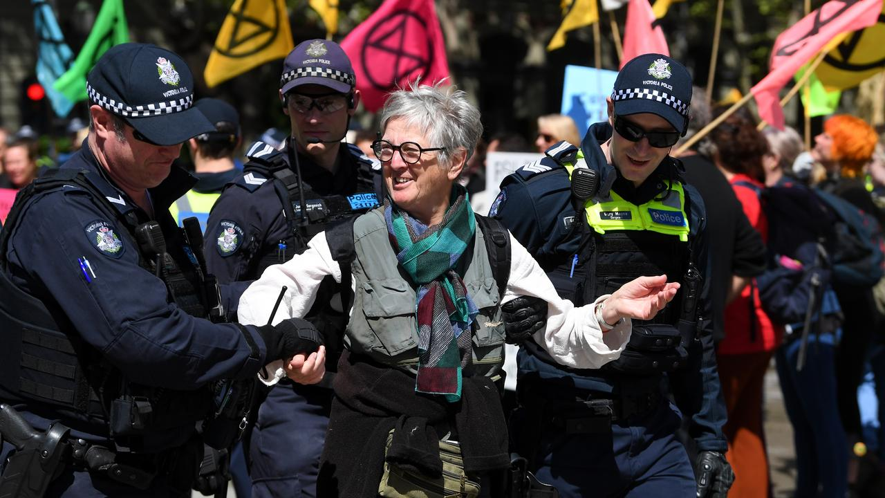 An Extinction Rebellion activist is escorted away by police. Picture: James Ross/AAP.