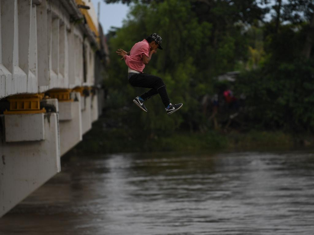 A Honduran migrant heading in a caravan to the US, jumps from the Guatemala-Mexico international border bridge. Picture: AFP