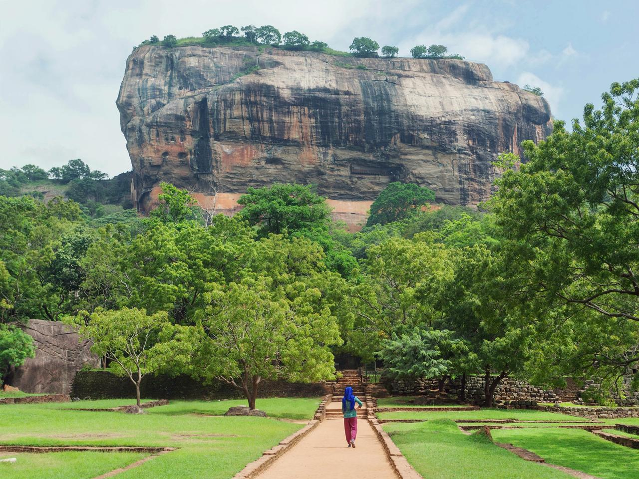 Lonely woman in headscarf walking to famous landmark Sigiriya rock with green trees forest around, Sri Lanka. UNESCO world heritage site