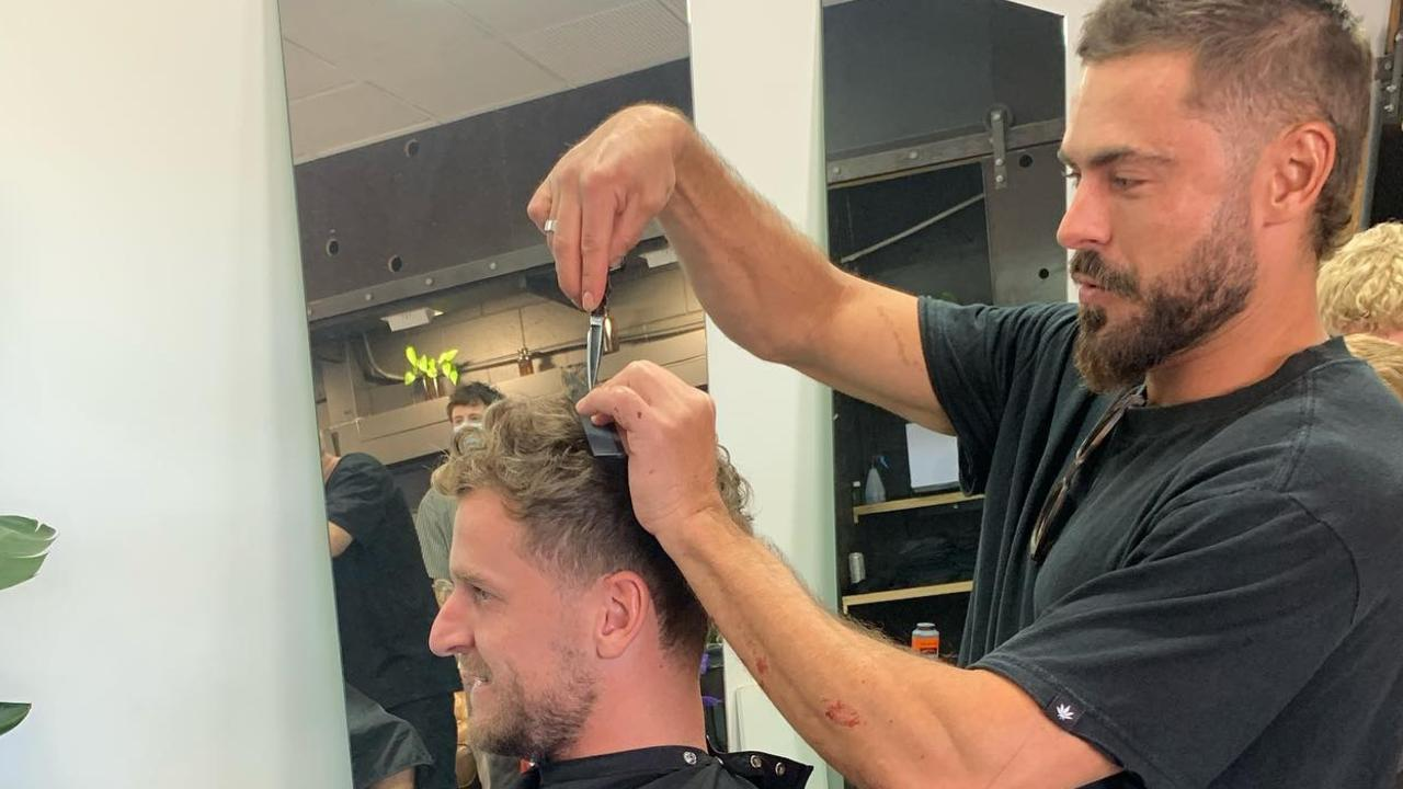 Zac lent a hand at cutting the barber shop owner's hair. Picture: Instagram.