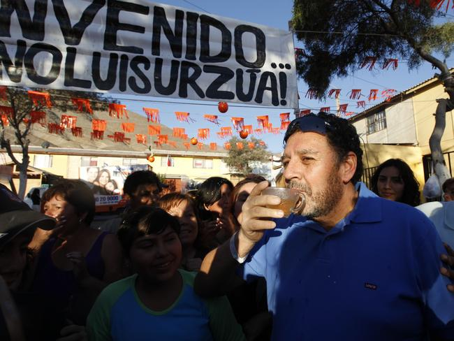 Luis Urzua drinks champagne after being welcomed home by neighbours. Pic: AP/Roberto Candia.