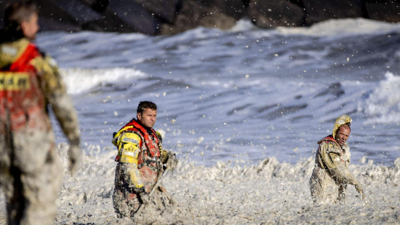Rescue workers stand in rough waters during the resumed search for missing water sports participants at Scheveningen, The Netherlands.