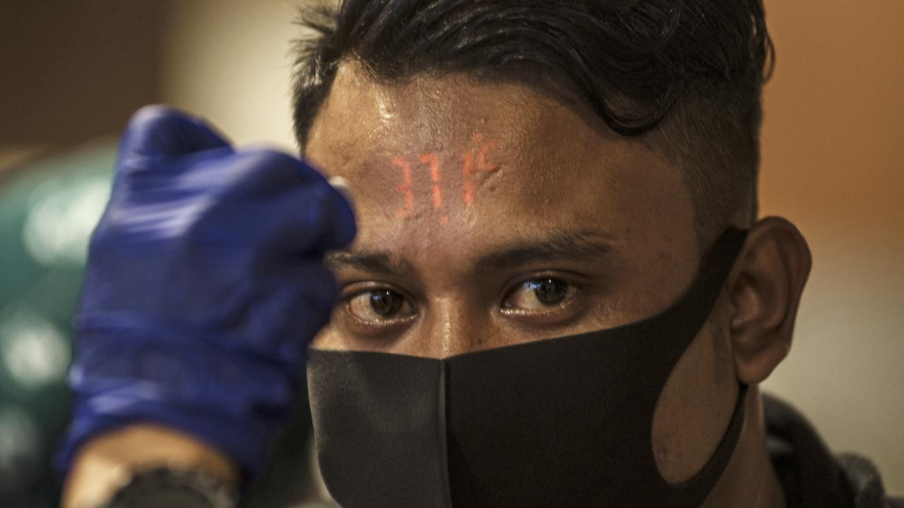 A traveller has his temperature checked upon arrival from Kuala Lumpur. Picture: AP Photo/Kusumadireza)