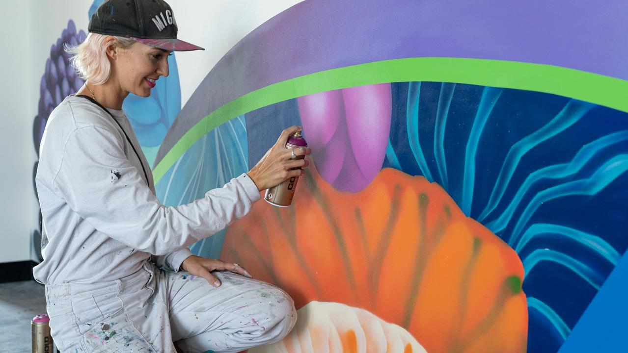 Artist Elle creates a colourful scene within another part of the development.