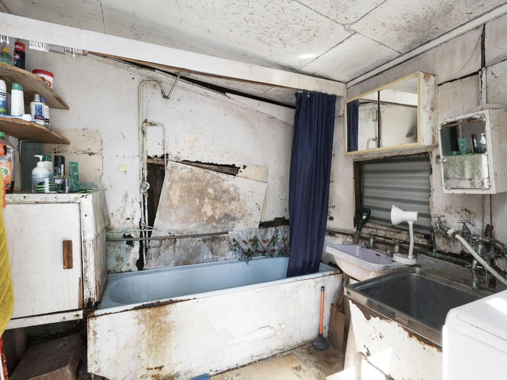 The bathroom and laundry is missing a wall and has mould on the ceiling.