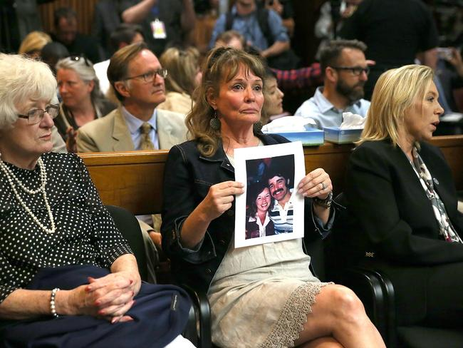 A woman holds a photo of Cheri Domingo and Gregory Sanchez, murdered in 1981, at the arraignment of Joseph James DeAngelo. Picture: Justin Sullivan/Getty/AFP