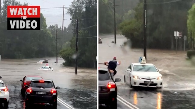 Moment taxi drives through flood water on Central Coast