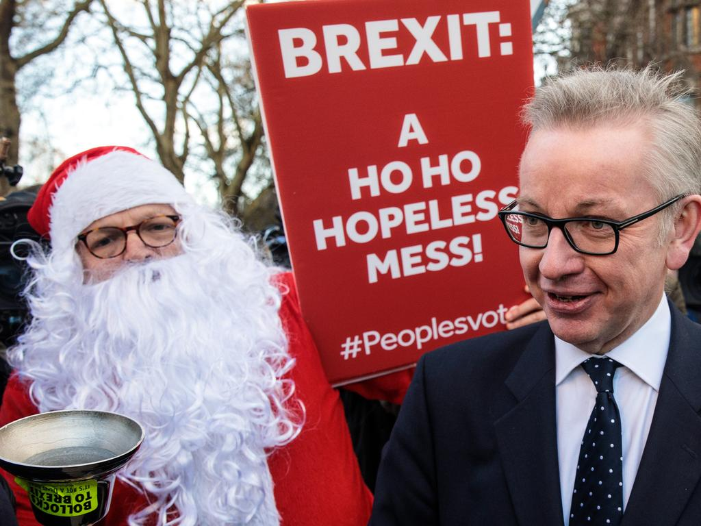 Environment Secretary Michael Gove is accosted by a protester in a Father Christmas outfit after speaking to the media in Westminster. Picture: Getty