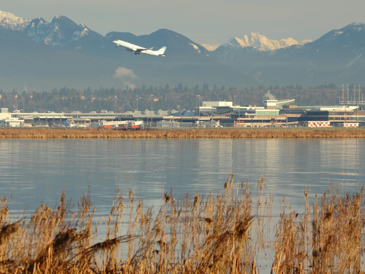 An airplane taking off at Vancouver International Airport, YVR, with the Coast Mountains in the background and the Fraser River in the foreground. British Columbia, Canada.