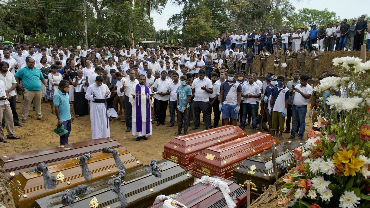 A priest conducts religious rituals during a mass burial for victims in Negombo. Picture: Gemunu Amarasinghe/AP