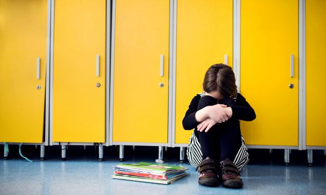 A sad small girl sitting on the floor at school by the lockers.