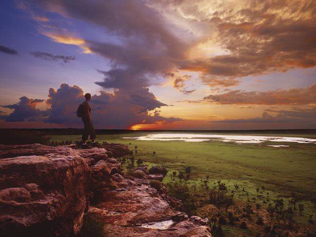"""4. WATCH THE SUN SET OVER UBIRR Ubirr is the rock formation in Kakadu National Park where Mick Dundee climbs to the top, points toward the horizon, and says """"This is my backyard, and over there is the Never Never"""" while the movie camera pans across the flood plain. One of the icons of Kakadu, Ubirr's rock art galleries contain a remarkable panoramic sweep of history with drawings ranging from the thylacine to the arrival of Europeans. Best time to visit is sunset, when the setting sun creates a rich palette of colours on the rock outcrops and the vast Nadab Plain below, where buffaloes in their thousands used to roam decades ago. Picture: Tourism NT"""