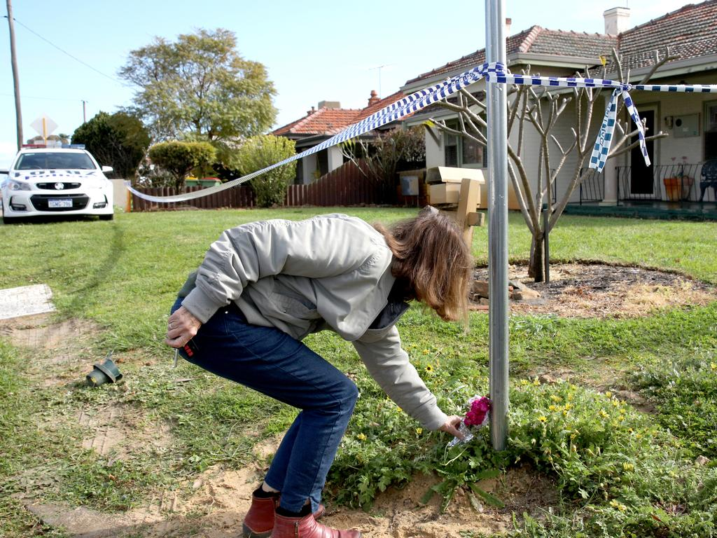 A member of the public lays flowers outside a property on Coode Street, Bedford. Picture: AP