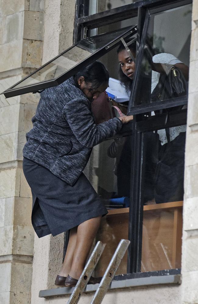 Civilians flee through a window at a hotel complex in Nairobi, Kenya. Picture: AP