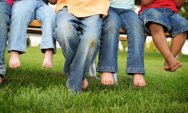 Dirty Legs and Feet of Children Sitting on a Bench