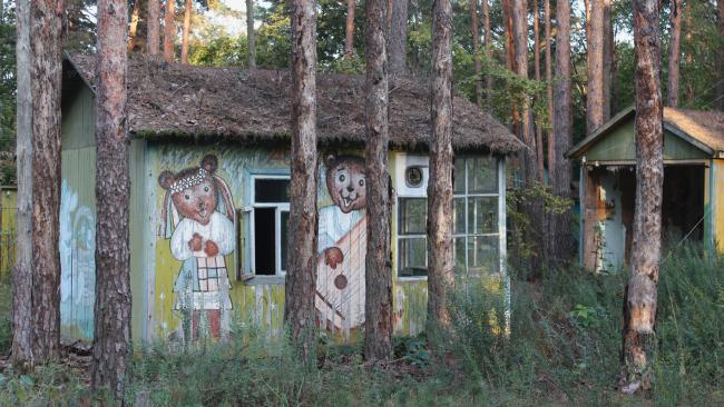 Izumrudniy' ('Emerald') Holiday Camp, near Chernobyl. Once a popular spot for summer holiday breaks, these rustic wooden chalets, painted with characters from cartoons and fairy tales, were completely destroyed by forest fires in April 2020. Picture: Darmon Richter/FUEL Publishing