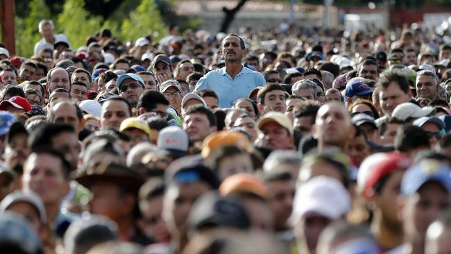 A man peeks over the crowd waiting to cross the border into Colombia through the Simon Bolivar bridge in San Antonio del Tachira, Venezuela Sunday July 17, 2016. Picture: Ariana Cubillos/AP