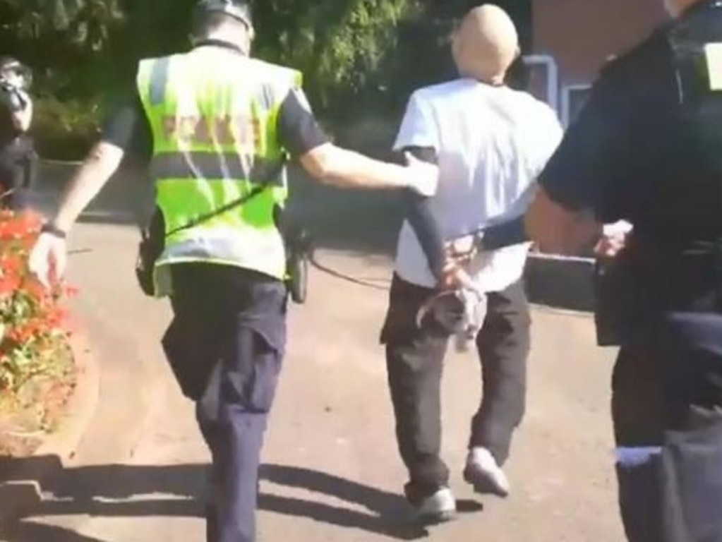 Video shows a man being walked away after being arrested in Brisbane Botanical Gardens for not wearing a mask.
