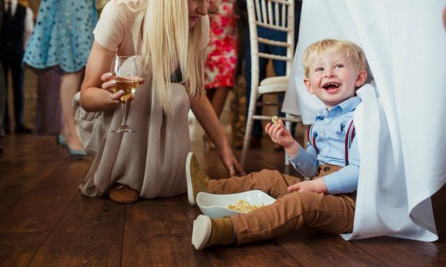 Young boy sitting under a table at a wedding reception with a bowl of snacks laughing. His mother is couching down beside him with a glass of wine in hand and smiling.