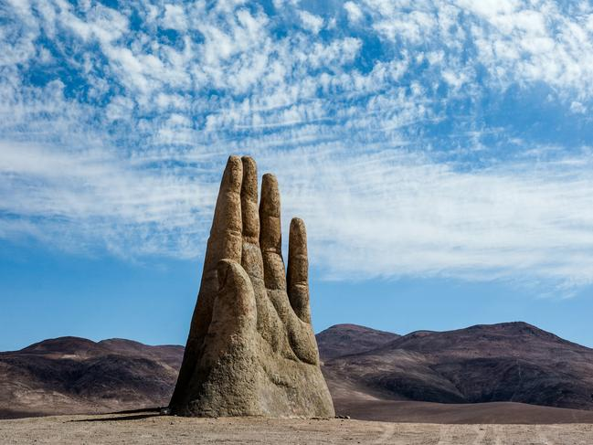 5/15Hand of the Desery, ChileEmerging from the ground in the middle of the Atacama Dessert are four concrete outstretched fingers and a thumb, considered by locals as a hi-5 from the land. The hand was constructed over 25 years ago by artist Mario Irarrázabal who intended for the isolated sculpture to represent human vulnerability and helplessness – two feelings anyone who has run out of petrol here can totally understand. LOCATION:  Antofagasta, Chile