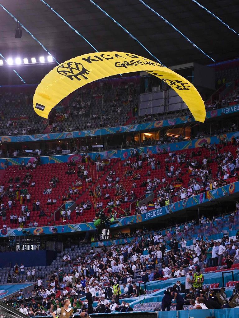 A paraglider flies into the stadium.