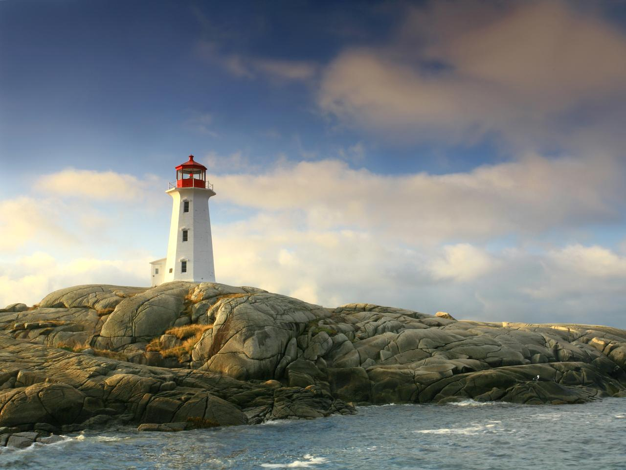The beautiful lighthouse at Peggy's Cove, Nova Scotia in dramatic morning light. This is one of the most famous lights in Canada and was also the scene of a tragic plane crash in the 90s. The water-worn rocks and dramatic lighthouse clutching the rocks are classic Canadiana. Thousands of people take the short drive from Halifax to visit Peggy's Cove, a classic fishing village, each year.