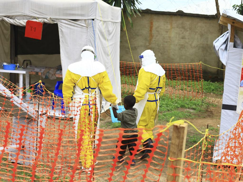 Health workers walk with a boy suspected of having the Ebola virus at a treatment centre in Beni, Eastern Congo. Picture: AP Photo/Al-hadji Kudra Maliro