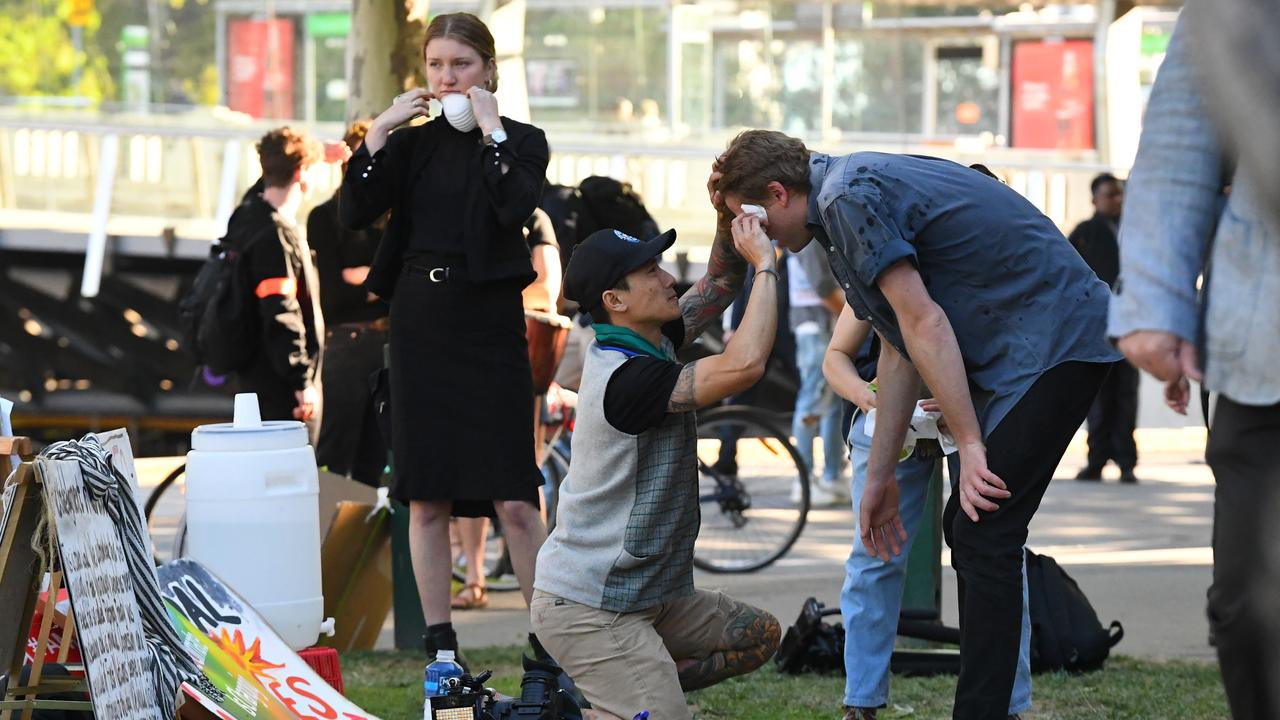 A cameraman (right) receives medical treatment from OC spray. Picture: James Ross/AAP