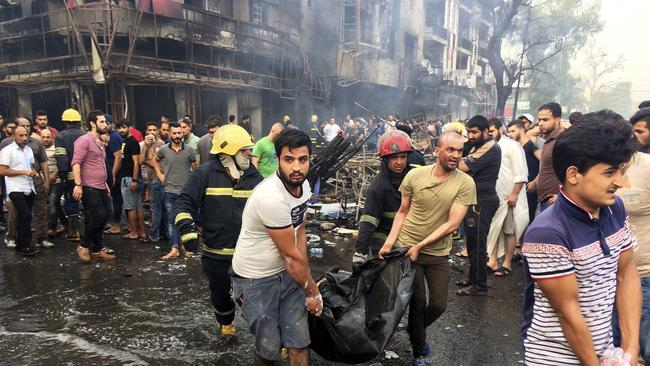 Iraqi firefighters and civilians carry the bodies of the victims from the scene.