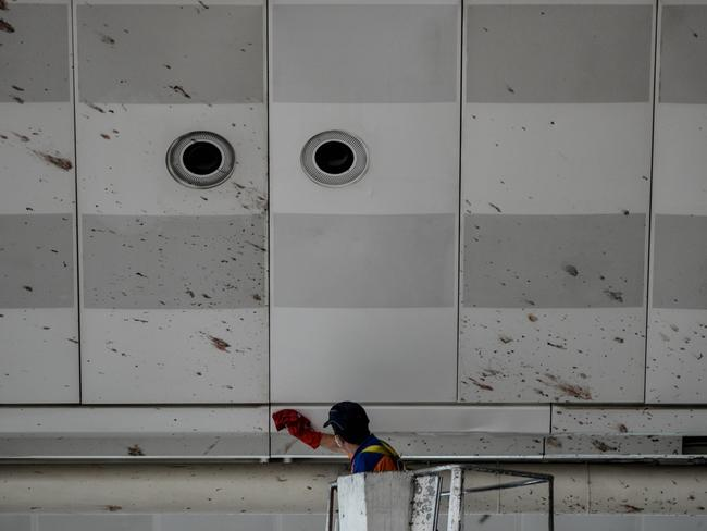 A worker cleans the blood splashed on the roof of the international departure terminal at the country's largest airport, Istanbul Ataturk. Picture: Getty