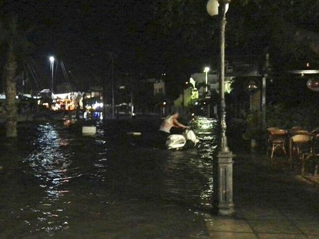 A man moves a scooter from a flooded coastal road after the earthquake on the Greek island of Kos. Picture: Kostoday.gr / AP