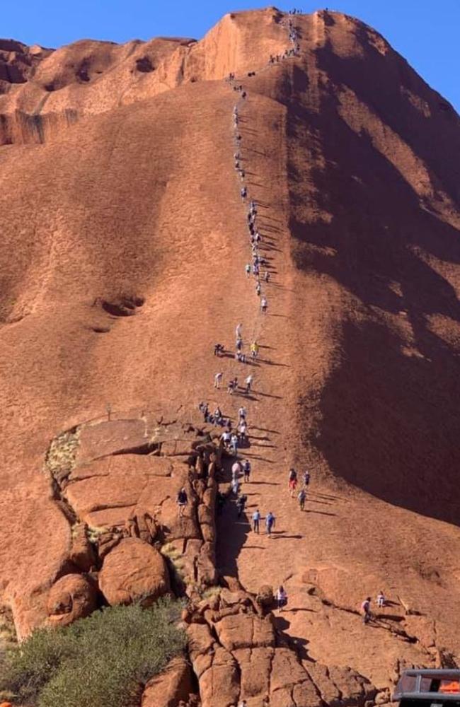 Dozens of tourists climbing Uluru.