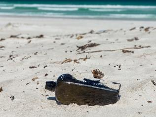 """A supplied image obtained on Tuesday, March 6, 2018, of the world?s oldest known message in a bottle which has been found half-buried at a West Australian beach nearly 132 years after it was tossed overboard into the Indian Ocean. The bottle had been flung from the German sailing barque """"Paula"""" in 1886 as part of a 69-year official experiment to better understand global ocean currents and find faster, more efficient shipping routes. (AAP Image/supplied/Kym Illman) NO ARCHIVING, EDITORIAL USE ONLY"""