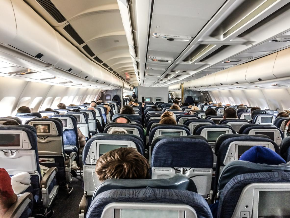 Passengers in a plane seen from behind, above seats