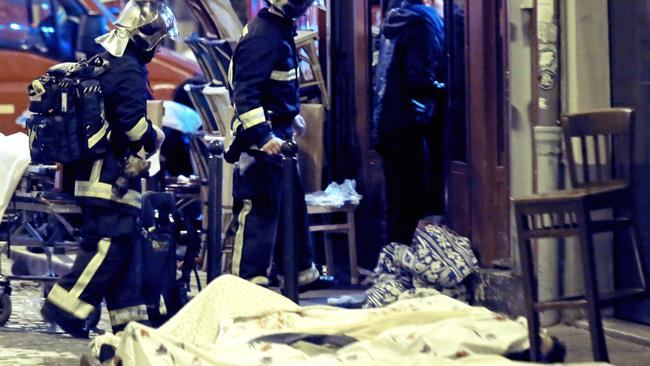 Rescue workers walk past victims in the 10th district of Paris. (AP Photo/Jacques Brinon)
