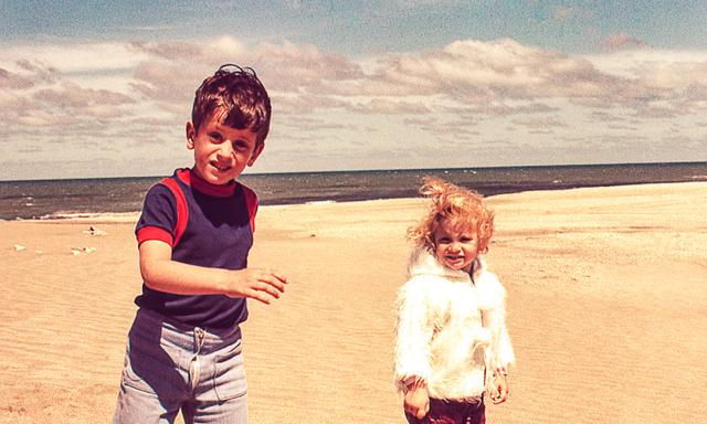 Vintage photo of a cute blonde little girl in with her brother at the beach on a cold day.