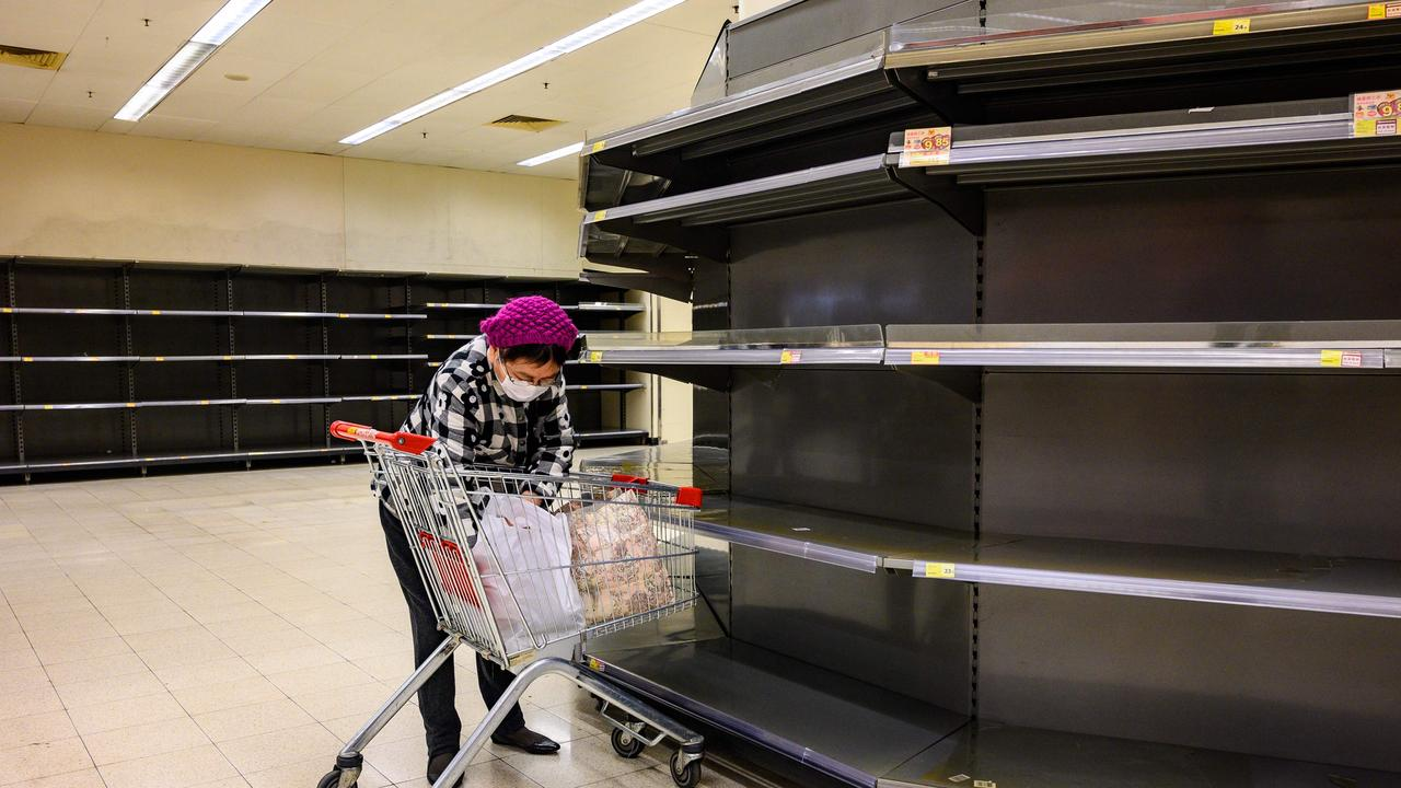 The COVID pandemic already saw food shortages and there will be more to come. A shopper next to bare supermarket shelves in Hong Kong on February 6. Picture: Philip FONG / AFP.