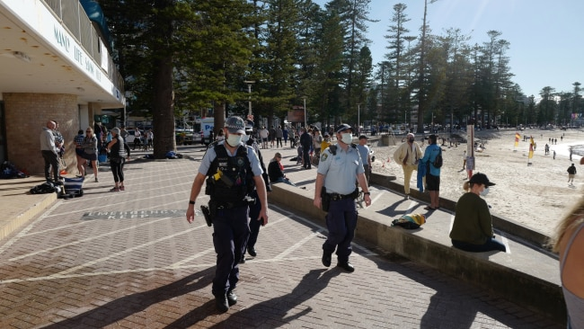 """Residents in Greater Sydney's coronavirus lockdown should """"expect a greater police presence"""", the Premier said. Police officers are seen patrolling Manly Beach on July 24. Picture: James D. Morgan/Getty Images"""
