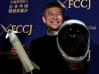 (FILES) This file photo taken on October 9, 2018 shows Yusaku Maezawa, entrepreneur and then-chief of online fashion company Zozo and SpaceX BFR's first private passenger, poses with a miniature rocket and space helmet prior to start of a press conference at the Foreign Correspondents' Club of Japan in Tokyo. - A Japanese billionaire has launched an online wanted ad -- a girlfriend who will fly around the Moon with him on a SpaceX rocket. The deadline to apply is January 17, 2020. (Photo by Toshifumi KITAMURA / AFP)