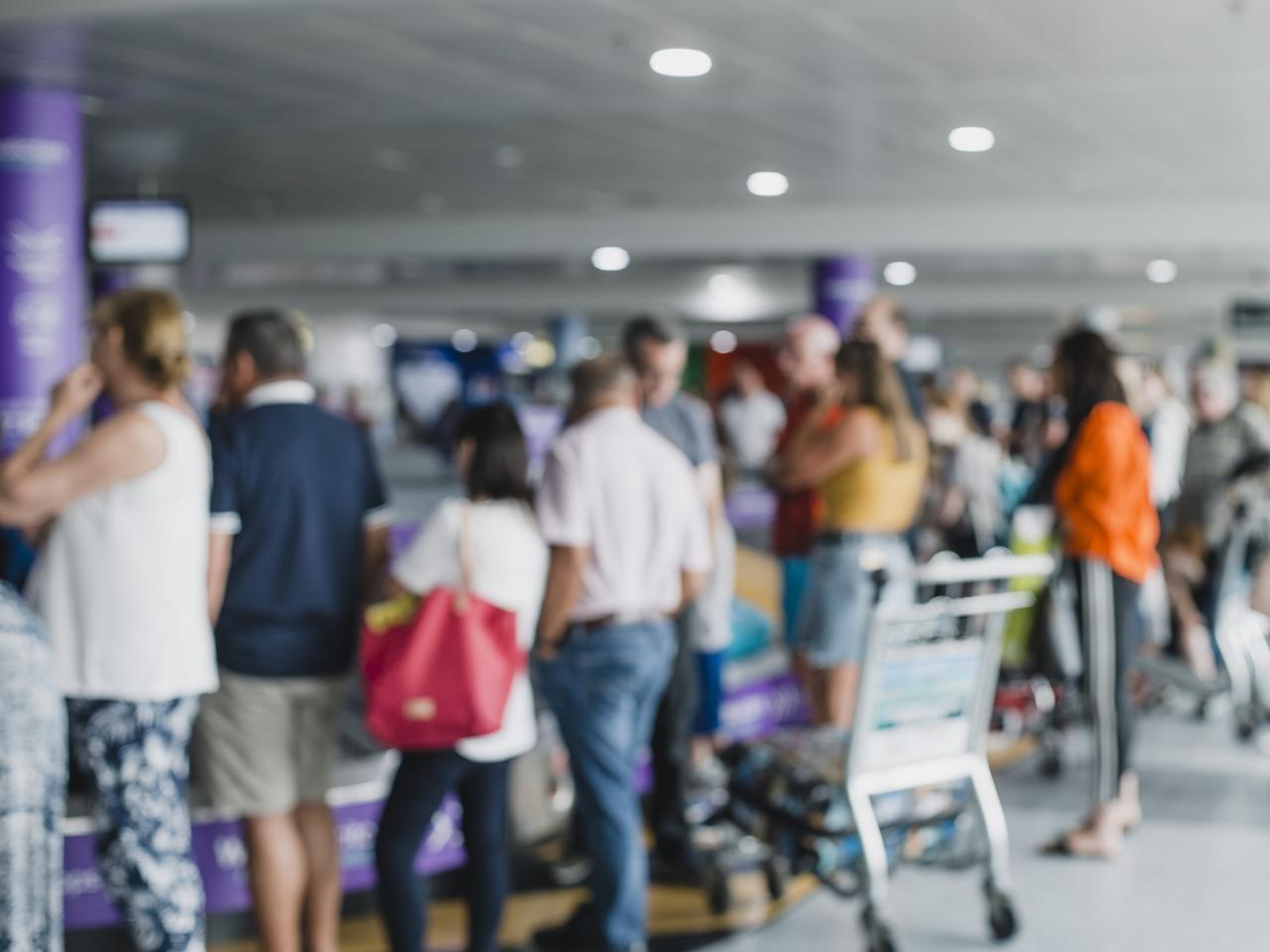 Defocused shot of people waiting to collect their luggage in an airport.