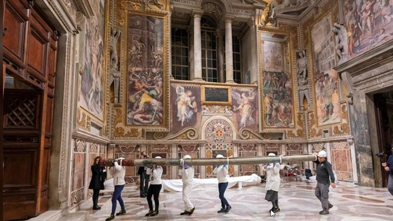 Workers bring in a Raphael tapestry to install on the lower wall of the Sistine Chapel. Picture: Reuters