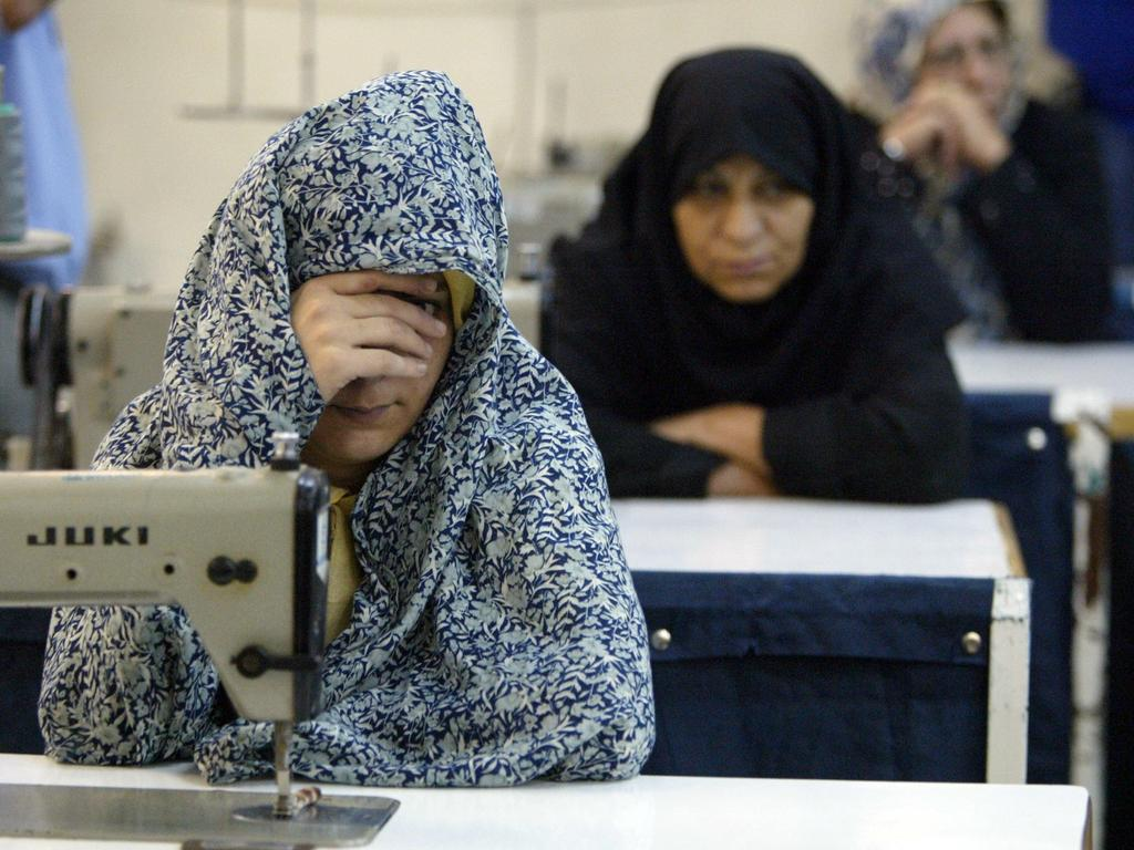 An Iranian woman prisoner covers her face as prisoners work with sewing machines in June 2006. Picture: Mohammad Kheirkhah/UPI Photo