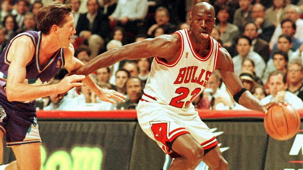 Former Chicago Bulls player Michael Jordan sticks out his tongue as he goes past Jeff Hornacek of the Utah Jazz during an NBA game in 1997. Picture: AFP