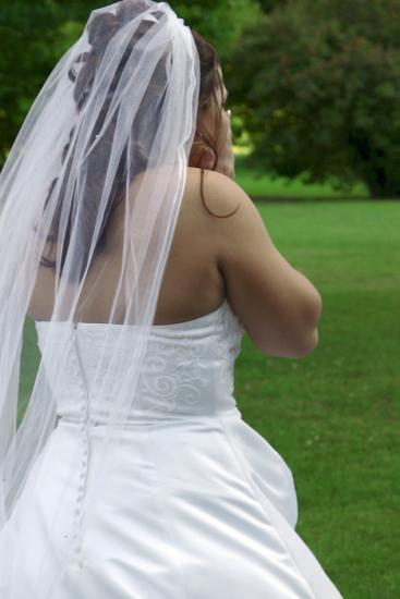 A surprised bride standing in the park. Focus is on the back of her dress.